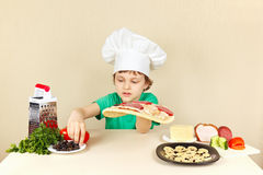 Young chef puts olives on pizza crust Stock Photography
