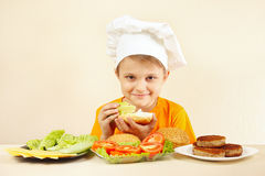 Young chef puts salad on big sandwich. Young chef puts salad on the big sandwich Royalty Free Stock Photo