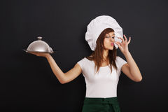 Young chef recommend main course. Young female cooking chef recommend main course royalty free stock photos