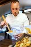 Young chef serving barbecue potatoes in a food truck. Portrait of young chef serving barbecue potatoes in a food truck Royalty Free Stock Photography