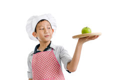 Young chef serving green apple on wooden tray Royalty Free Stock Photography