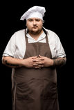 Young chef standing in hat and apron isolated on black. Professional young chef standing in hat and apron isolated on black royalty free stock photo