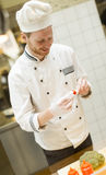 Young chef standing in a modern kitchen in the restaurant and pr. Young chef with white uniform standing at a modern kitchen in the restaurant and preparing food stock photos