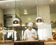 Young chef standing in a modern kitchen in the restaurant and pr Stock Photo