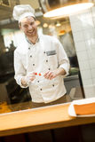 Young chef standing in a modern kitchen in the restaurant and pr. Young chef with white uniform standing at a modern kitchen in the restaurant and preparing food royalty free stock images