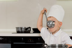 Young chef tasting soup from ladle Stock Image
