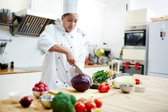 Chef at work. Young chef in uniform cutting fresh cabbage in two halves while preparing vegetarian food Royalty Free Stock Images