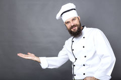 Young chef in uniform invite you in. Over gray background Stock Photos