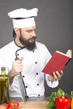 Young chef in uniform reading a recipe, ready to cook Royalty Free Stock Photos
