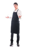 Young chef or waiter wearing black apron isolated. Young chef posing wearing black and white dress isolated in white background stock photo