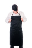 Young chef or waiter wearing black apron isolated. Young chef or waiter posing, wearing black apron and white shirt isolated on white background royalty free stock images