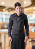 Young chef or waiter wearing black apron in restaurant Royalty Free Stock Photo