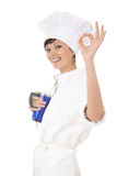 Young chef woman with blue cup and ok. sign Royalty Free Stock Image