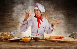 Young chef woman cooker ready for food preparation. Raw ingredients served on wooden table, blur brick wall on background royalty free stock photos