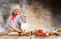 Young chef woman cooker ready for food preparation. Raw ingredients served on wooden table, blur brick wall on background royalty free stock photo