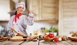 Young chef woman cooker ready for food preparation. Raw ingredients served on wooden table, blur modern kitchen on background stock photo