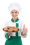 Young chef woman in uniform holding tray with muffins and thumbs Royalty Free Stock Image