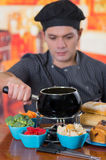 Young cheff preparing a gourmet Swiss fondue dinner with assorted cheeses and a heated pot of cheese fondue and some Stock Photo