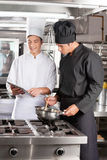 Young Chefs With Digital Tablet Preparing Food Royalty Free Stock Photos