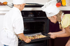 Young chefs placing their pizzas in the oven Stock Photos