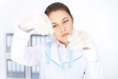 Young chemical female researcher holding two glass tubes Stock Photo