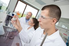 Young chemist combining chemical liquid in lab Royalty Free Stock Photos