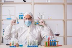 Young male chemist in drugs synthesis concept