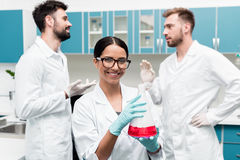 Young chemist holding flask with reagent while colleagues talking behind in lab. Smiling young chemist holding flask with reagent while colleagues talking behind Stock Photo