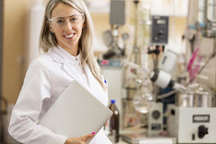 Young chemist with laptop computer standing in chemistry lab Stock Image