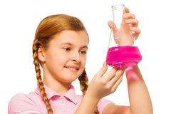 Young chemist pouring pink reagent in glass retort Royalty Free Stock Photos