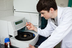 Young chemist using a centrifuge Stock Photography
