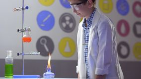 Young chemist works in laboratory. The boy in protective glasses looks at the chemical flasks with liquid. Cute boy touches bulb with orange liquid. Chemical stock video footage