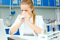 Young chemistry teacher in school laboratory workplace ill. Young female chemistry biology teacher in school laboratory sitting at workplace feeling unwell ill Stock Photos