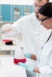 Young chemists in eyeglasses and white coats making experiment with reagents and flasks Royalty Free Stock Photos