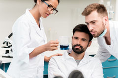 Young chemists in lab coats making working with reagent in laboratory. Professional young chemists in lab coats making working with reagent in laboratory Stock Images