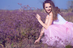 Young chic woman with long waving hair and artistic make up sitting on the field of violet flowers looking aside and smiling. Stock Photography