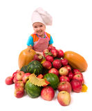Young chief cook. Happy smiling girl with lots of fruits royalty free stock photos