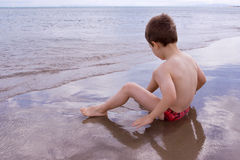 Young child alone on the beach Royalty Free Stock Images
