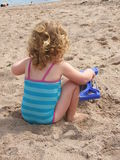 Young child on a beach. Young child playing in the sand on a beach in the UK Royalty Free Stock Photo