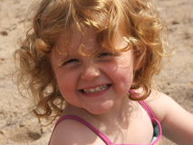 Young child on a beach. Young child plays happily in the sand in Summertime on a beach in Devon UK smiling Stock Images
