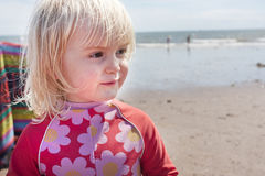 Young child on the beach in summer wearing flowery wetsuit Stock Photos