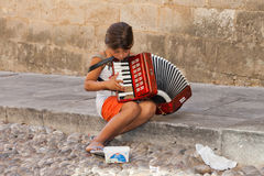 Young child beggar, playing music in the streets Stock Photography