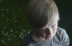 Young child blond boy sad and crying in the garden in summer Royalty Free Stock Photos