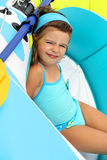 Young child in a boat. Young child in swimsuit relaxing inside a colorful rubber boat Stock Image