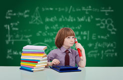 Young child with books in front of blackboard Royalty Free Stock Photos
