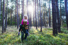 Young child boy giving his sister piggyback outdoors in the forest. Children in nature, wounded girl Royalty Free Stock Photography