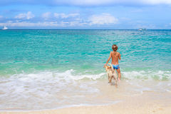Young child boy having fun with white dog in the sea, summ. Young happy child boy having fun with white dog in the sea, summer vacation Royalty Free Stock Photography