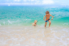 Young child boy having fun with white dog in the sea, summ Stock Images