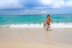 Young child boy having fun with white dog in the sea, summ Stock Photos
