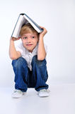 Young child boy. Hide with book Royalty Free Stock Photo
